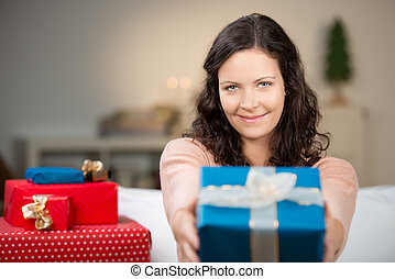 Woman Giving Christmas Gift At Home