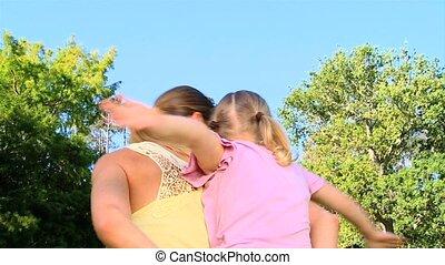 Woman giving daughter a piggy back