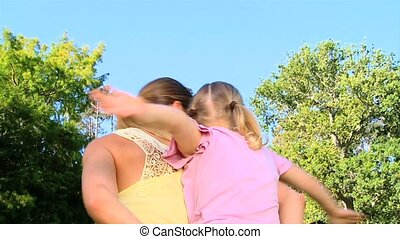 Woman giving daughter a piggy back