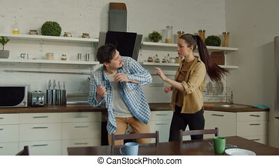 Woman giving fight to man aggressor in kitchen - Angry...
