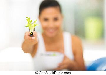 woman giving fresh green salad