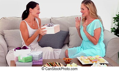 Woman giving her friend a present o