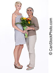Woman giving her grandmother flowers