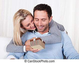 Woman giving her husband a surprise gift