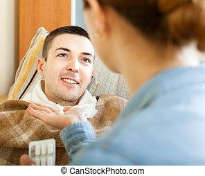 Woman giving pills man