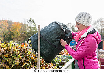 Woman giving waste green in container at recycling center -...