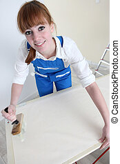 Woman gluing length of wallpaper