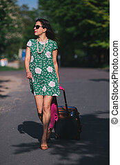 Woman goes along the road with a suitcase