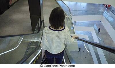 Woman goes down on an escalator