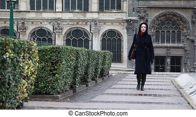 Woman goes on square from ancient cathedral