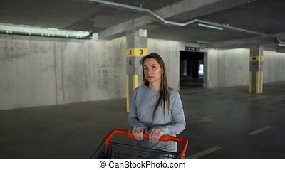 Woman with groceries goes through an underground parking lot with a shopping cart