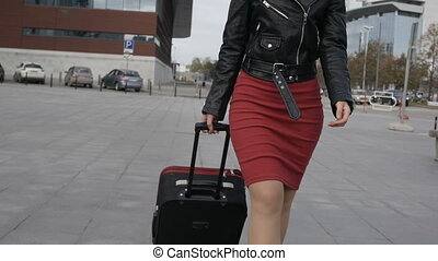 Woman goes with red suitcase