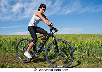 woman going for bike ride on sunny day in countryside