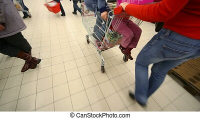 woman going in mall with kids on shopping trolley