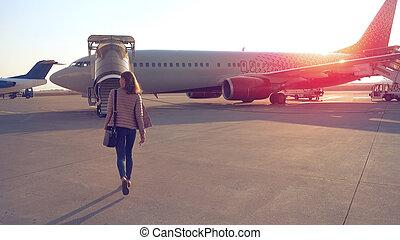 Woman going to plane an aerodrome