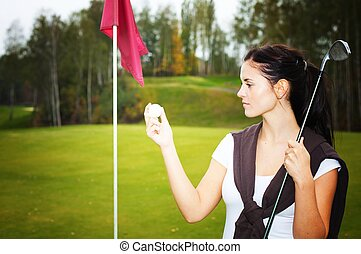 Woman golf player on green looking at ball