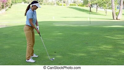 Woman golfer about to play a stroke on the green