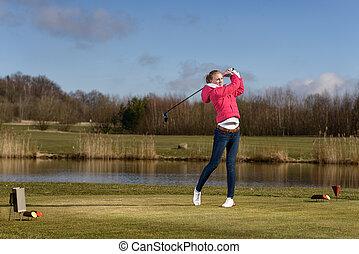 Woman golfer hitting a golf ball on the fairway