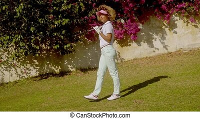 Woman golfer posing in front of bougainvillea