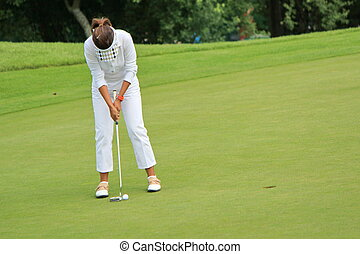 Woman golfer putting on the green