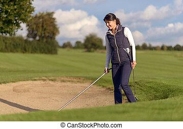 Woman golfer raking a sand bunker