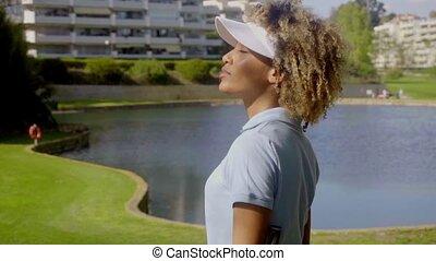 Woman golfer walking beside a lake or water hazard on the...
