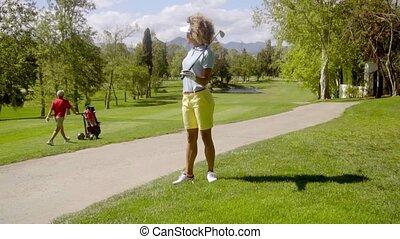Woman golfer watching a man pushing a golf cart