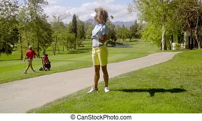 Woman golfer watching a man pushing a golf cart on the...