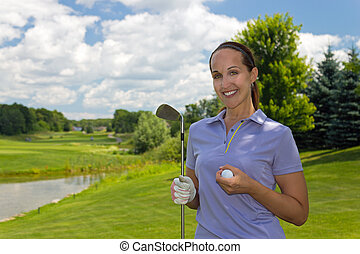 Woman golfer with golf club and ball on the fairway