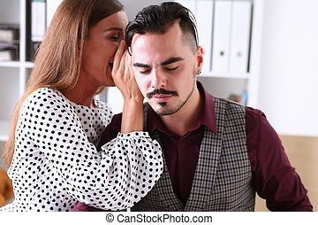 Woman gossip whispers in the ear of news to a man in office