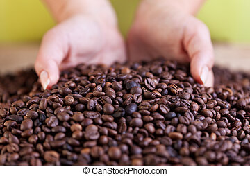Woman grabbing a handful of roasted coffee beans