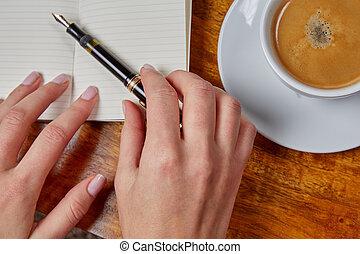 Woman grabs fountain pen on a notebook