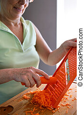 Woman grating a carrot