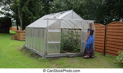 woman greenhouse door - Blond woman in dress close...