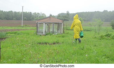 woman greenhouse rain - Woman in waterproof coat walk with...