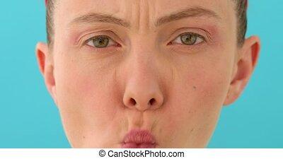 Woman grimaces close up - Woman posing at blank studio wall,...