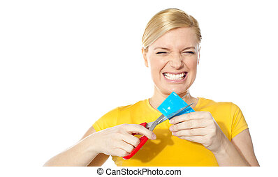 Woman grinding teeth while cutting her credit card isolated ...