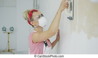 Woman grinding wall with sandpaper - Side view of blond...