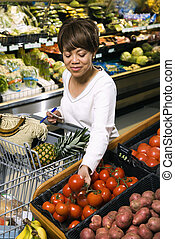 Woman grocery shopping. - Middle aged African American woman...