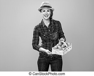 woman grower isolated on yellow background basket with eggs