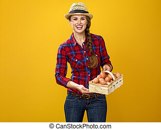 woman grower isolated on yellow background basket with eggs...