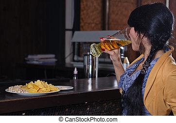 Woman gulping down a beer at the bar
