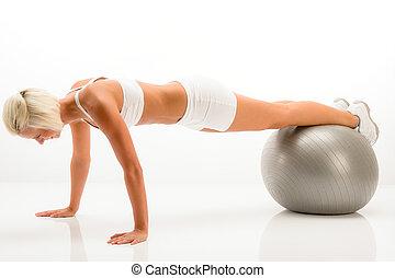 Woman gym ball pushups at white fitness - Sportive woman...