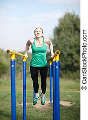 Woman gymnast exercising on parallel bars