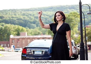 Woman Hailing a Taxi Cab - A beautiful brunette woman waving...