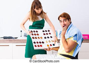 Woman hairdresser applying dye to man hair