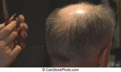 Woman hairdresser cuts a man with receding hairline with...
