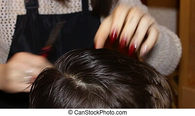 Woman hairdresser cuts boy - Woman hairdresser cuts with...