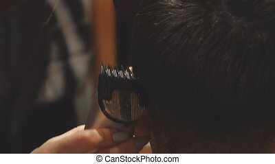 Woman Hairdresser cuts man's hair with electric clipper...