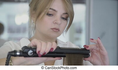 Woman hairdresser straightens hair using curling iron in beauty salon.